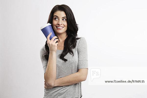 Porträt einer lächelnden jungen Frau mit Kaffee zum Mitnehmen