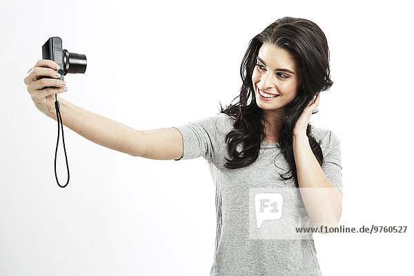 Portrait of young woman taking a selfie with camera