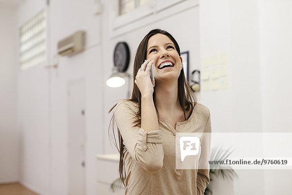Junge Unternehmerin telefoniert mit Smartphone im Home Office