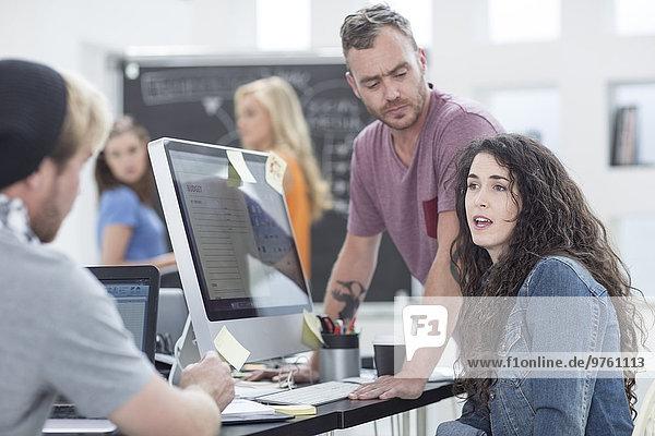 Kreative Büromenschen diskutieren am Schreibtisch