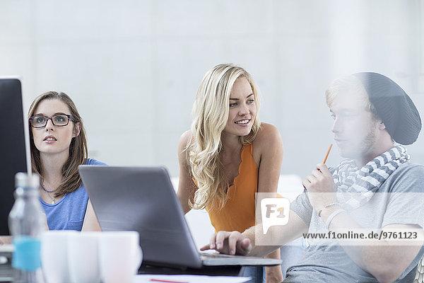 Kreative Büromenschen beim Diskutieren und Arbeiten am Laptop