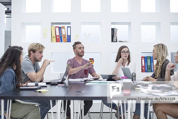 Kreative Büromenschen bei einer Besprechung am Besprechungstisch