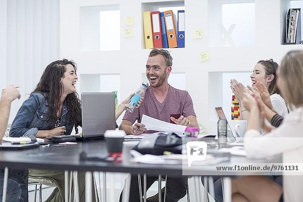 Kreative Büromenschen applaudieren ihrem Kollegen