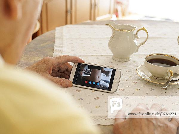 Großvater Videokonferenz mit schwangerer Enkelin via Smartphone