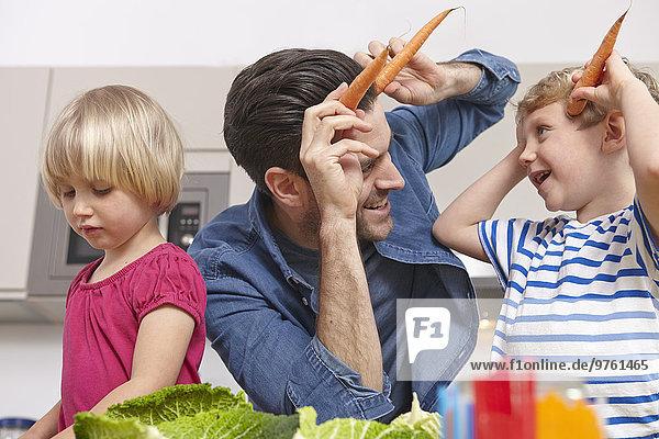 Vater spielt mit den Kindern in der Küche und macht Karottenhörner.