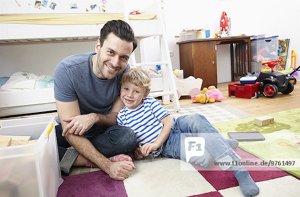 Father and son playing together in kid's room