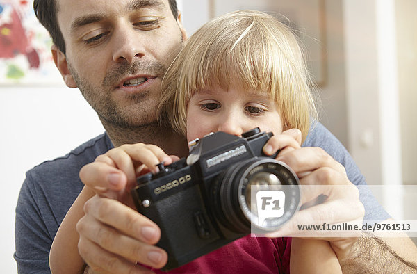Vater erklärt der Tochter die analoge Kamera