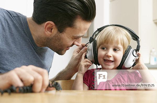 Vater und Tochter hören Musik über Kopfhörer