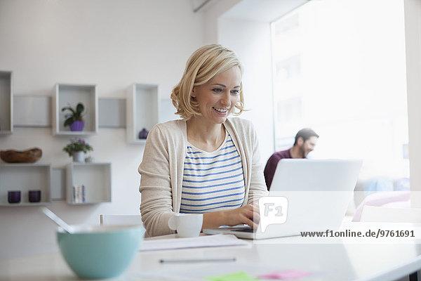 Porträt einer Frau bei der Arbeit mit dem Laptop im Homeoffice
