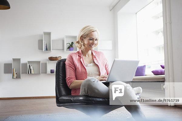 Frau sitzend mit Laptop auf Lederstuhl zu Hause