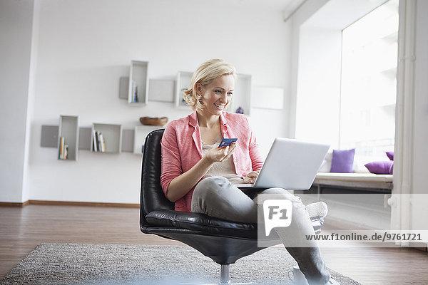 Frau mit Laptop und Kreditkarte sitzt zu Hause auf Lederstuhl