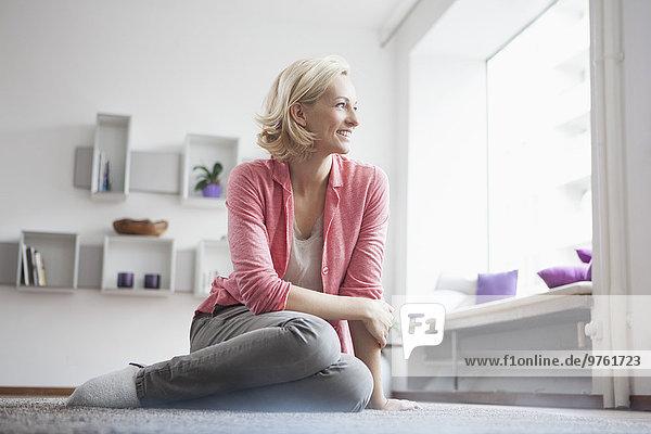 Frau sitzend auf Teppich im Wohnzimmer
