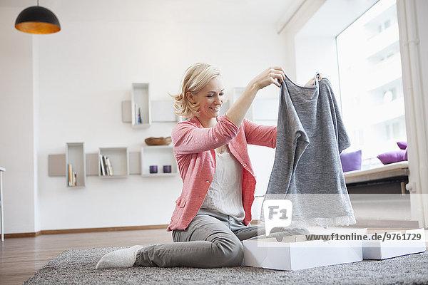 Frau mit Einkauf im Wohnzimmer
