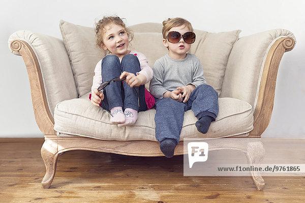 Bruder und Schwester mit übergroßer Sonnenbrille auf der Couch sitzend Bruder und Schwester mit übergroßer Sonnenbrille auf der Couch sitzend