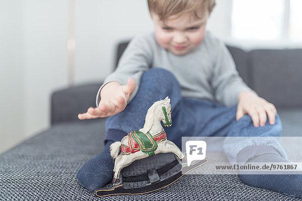 Kleiner Junge spielt mit hölzernem Schaukelpferd