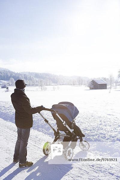 Österreich  Land Salzburg  Steinernes Meer  Mutter mit Kinderwagen im Winter