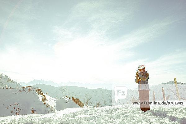 Österreich  Land Salzburg  Region Hochkönig  junge Skifahrerin beim Fotografieren mit Smartphone