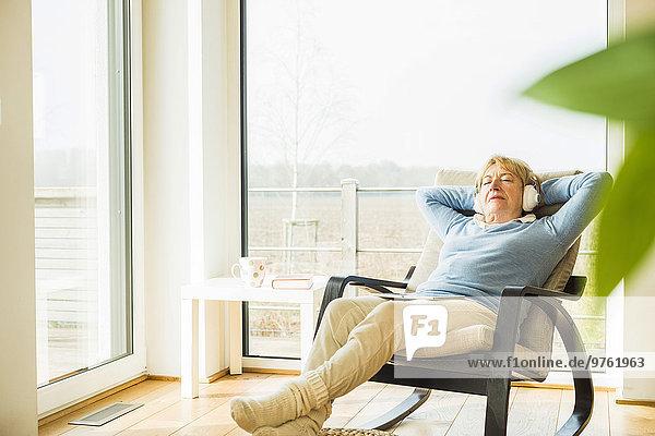 Seniorin zu Hause entspannt mit Kopfhörern