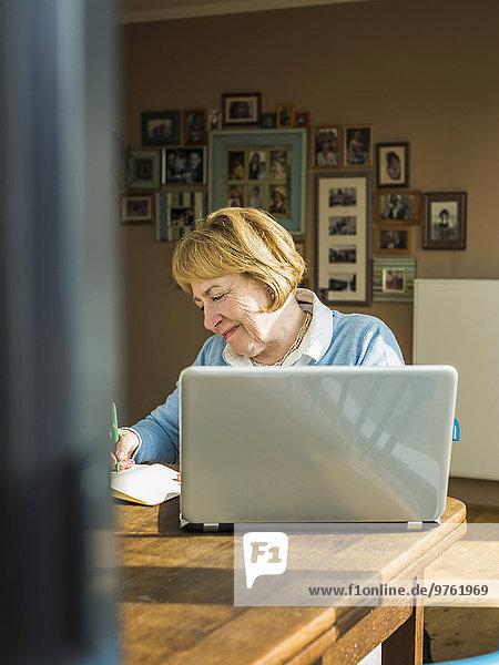Seniorin zu Hause mit Laptop und Notebook
