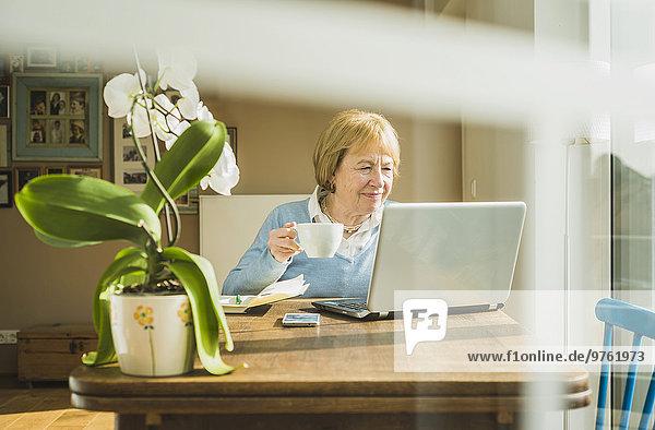 Seniorin zu Hause mit Laptop und Tasse Kaffee