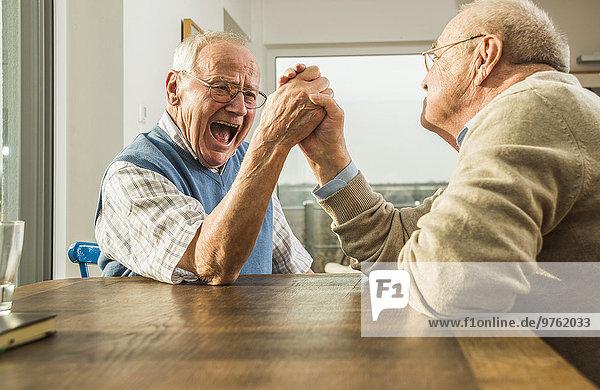 Zwei ältere Freunde Armdrücken