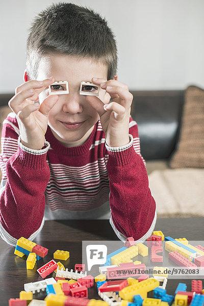 Junge spielt mit Bausteinen auf einem Tisch