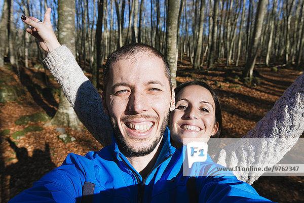 Porträt eines glücklichen Paares mit einem Selfie im Wald