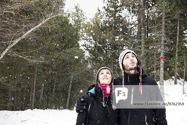 Lächelndes Paar im Wald im Winter