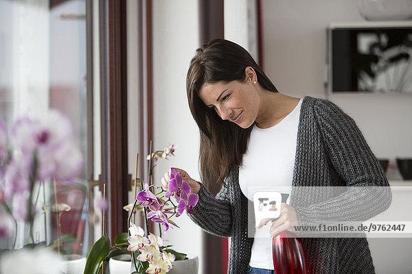 Frau mit Sprühflasche beobachtet Orchidee