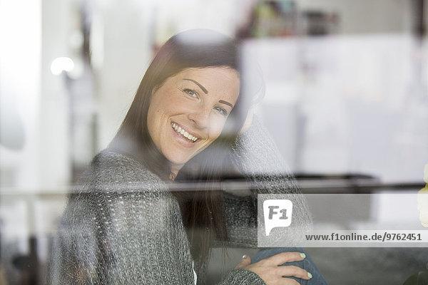 Smiling woman looking through window