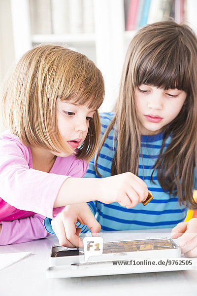 Two girls with box of letter stamps