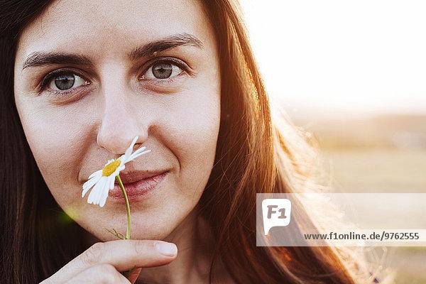 Porträt einer lächelnden Frau  die Blume riecht