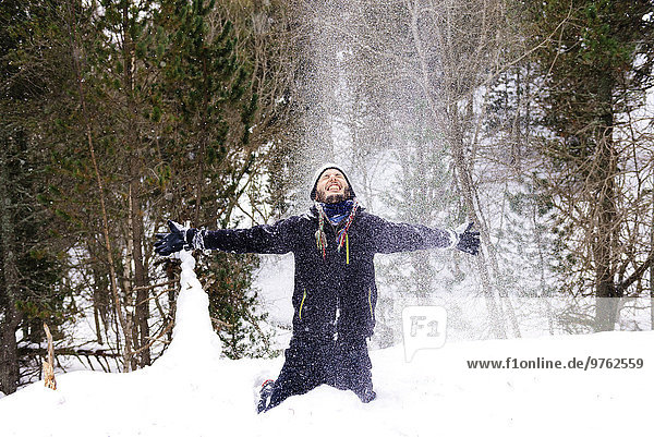 Man playing with the snow in forest