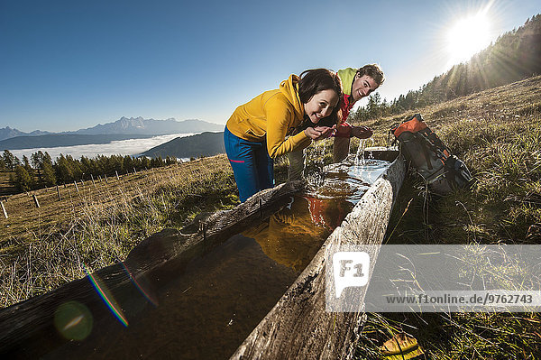 Österreich  Altenmarkt-Zauchensee  junges Paar erfrischend an der Wasserstelle