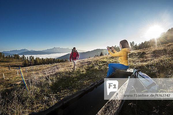 Österreich  Altenmarkt-Zauchensee  junges Paar fotografiert auf Wanderung in den Niederen Tauern