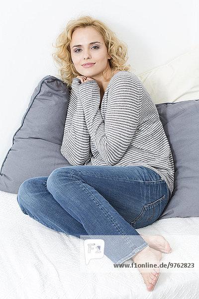 Lächelnde blonde junge Frau auf der Couch
