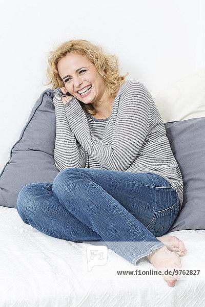 Fröhliche blonde junge Frau auf der Couch