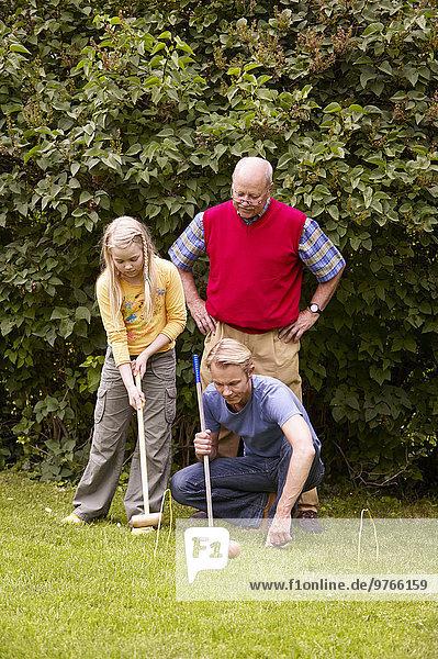 Großvater  Vater und Tochter spielen Krocket im Garten