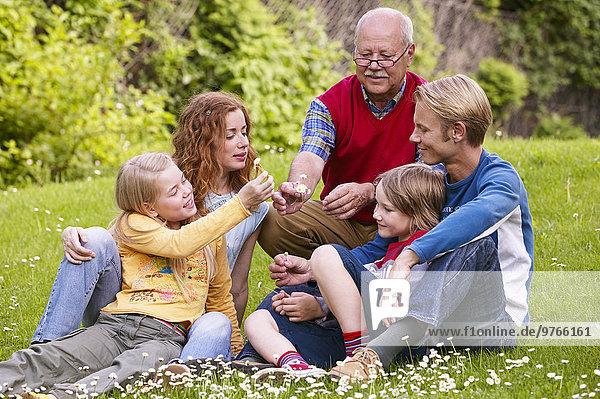 Dreigenerationen-Familie sitzt im Garten