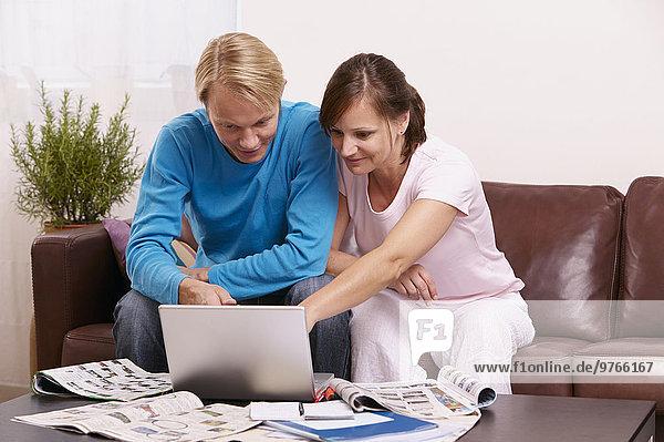 Paar mit Laptop und Zeitschriften auf der Couch