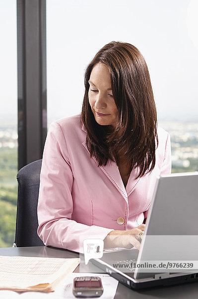 Geschäftsfrau im Büro mit Laptop und Zeitung