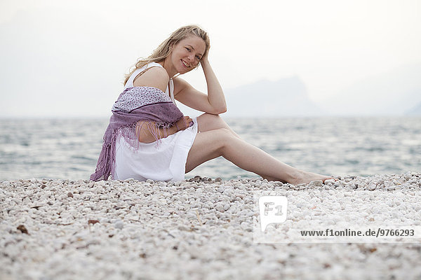 Lächelnde blonde Frau sitzt am Gardasee  Italien