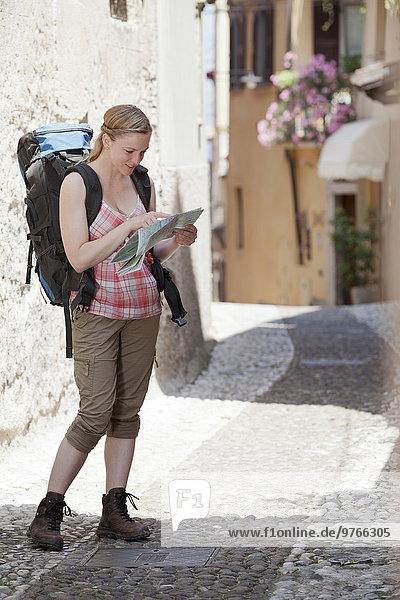Frau mit Rucksack schaut auf eine Landkarte  Garda  Italien