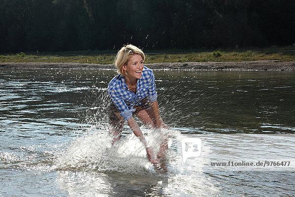 Woman splashing water in River Isar  Munich  Germany