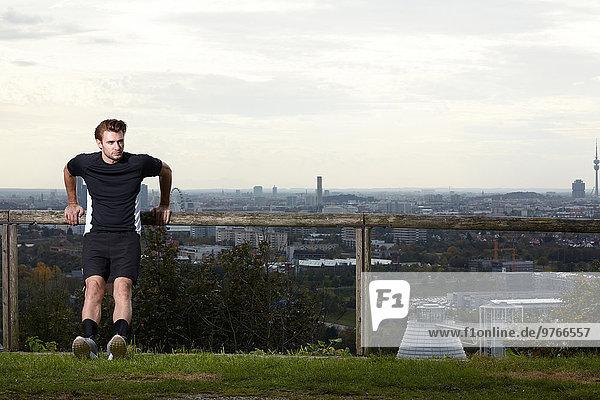 Sportlicher junger Mann dehnt sich mit der Skyline von München im Hintergrund  Bayern  Deutschland