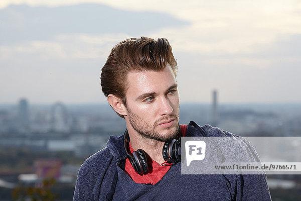 Junger Mann mit Kopfhörern im Freien