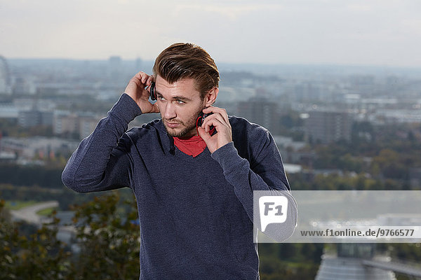 Young man with headphones with skyline of Munich in background  Bavaria  Germany