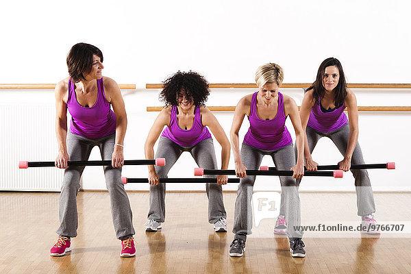Vier Frauen trainieren mit einem Stab in einem Fitnessstudio