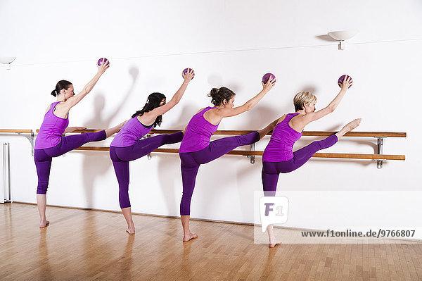 Vier Frauen trainieren mit Bällen an einer Ballettstange