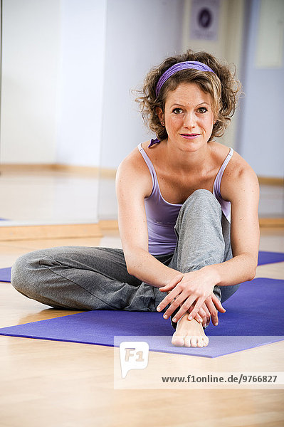 Lächelnde Frau auf einer Gymnastikmatte